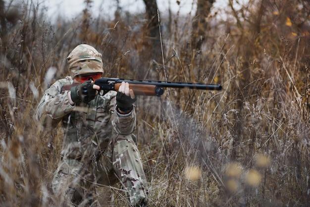 Koncepcja polowania, wojny, armii i ludzi - młody żołnierz, strażnik lub myśliwy z pistoletem spacerującym po lesie