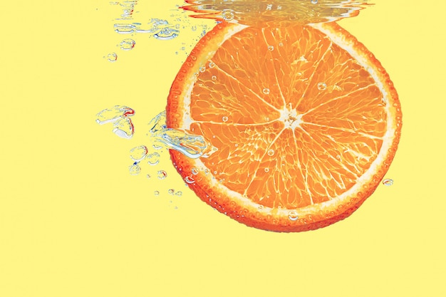 Koncepcja pomarańczy wpadających do wody na żółtym tle błyszczące z bąbelkami