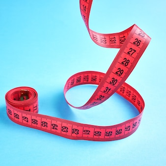 Koncepcja pomiaru utraty wagi. czerwony centymetr balansujący na niebieskim