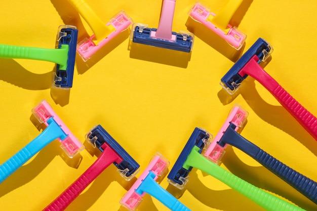 Koncepcja pop-artu uroda i moda. wiele kolorowych plastikowych maszynek do golenia na czerwono. minimalizm. widok z góry.