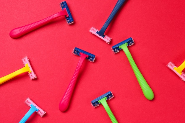 Koncepcja pop-artu uroda i moda. wiele kolorowych plastikowych maszynek do golenia na czerwono. minimalizm