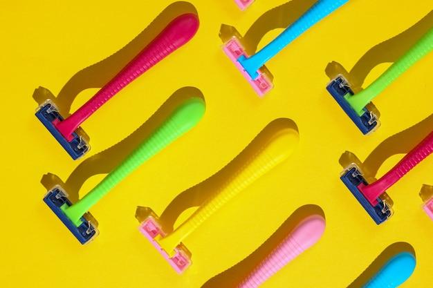 Koncepcja pop-artu uroda i moda. wiele kolorowych plastikowych maszynek do golenia na żółto.