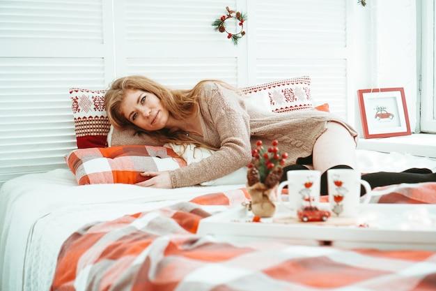 Koncepcja poranka, wypoczynku, świąt bożego narodzenia, zimy i ludzi - szczęśliwa młoda kobieta w łóżku w sypialni w domu
