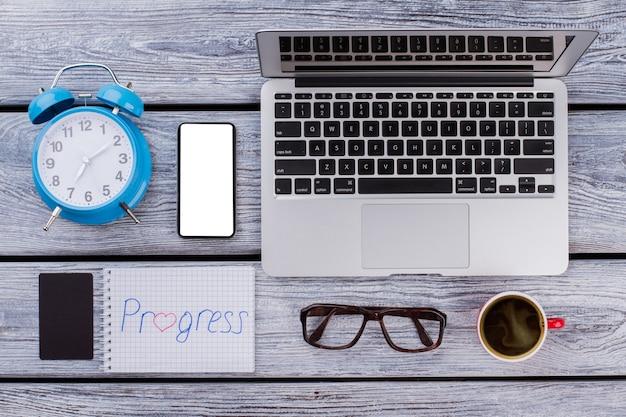 Koncepcja postępu pracy. mieszkanie świeckich cyfrowych przedmiotów i filiżankę kawy na białym drewnianym stole.