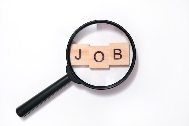 Koncepcja poszukiwania pracy. napis pracy na stole, wiele arkuszy z literami, szkło powiększające, sporządzanie życiorysu