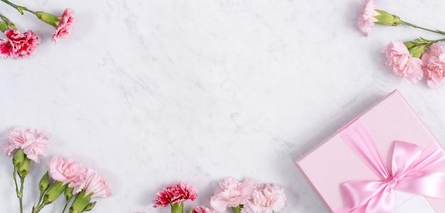 Koncepcja pozdrowienia projekt prezent świąteczny dzień matki z bukietem goździków na białym tle marmuru