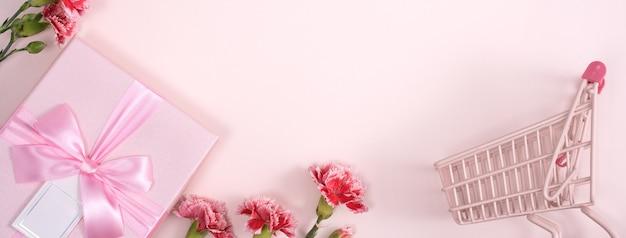 Koncepcja pozdrowienia wakacje dzień matki z bukietem goździków i prezentem na różowym tle