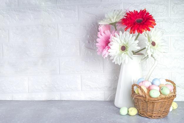 Koncepcja pozdrowienia wielkanocne. świąteczne tło wielkanoc z wiosennych kwiatów, malowane kolorowe jajka w koszu.