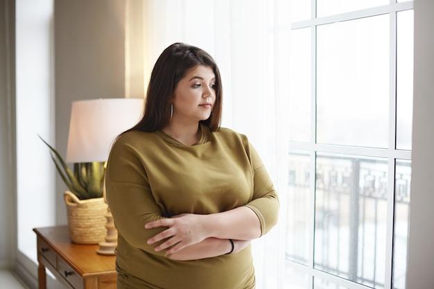 Koncepcja pozytywnej postawy ludzi, stylu życia i ciała. piękna młoda brunetka z dodatkowymi kilogramami stoi przy oknie w domu, krzyżuje ramiona na piersi, ma zamyślony wygląd, rozmyślając