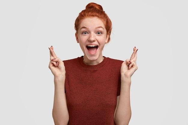 Koncepcja pozytywnych ludzkich emocji i uczuć. wesoła piegowata rudowłosa dziewczyna otwiera usta ze szczęścia, krzyżuje palce