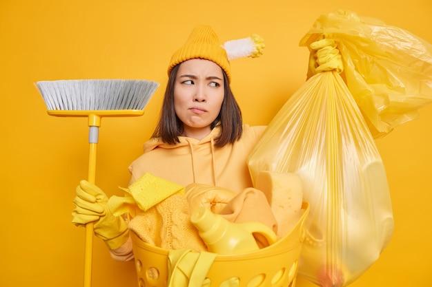 Koncepcja prac domowych. niezadowolona gospodyni zamierza wynieść śmieci z domu zamiata podłogę z miotłą pozuje w pobliżu kosza pełnego prania i detergentów odizolowanego na żółtym tle