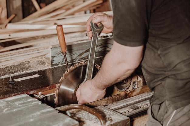 Koncepcja prac stolarskich i stolarskich, profesjonalny stolarz, stolarz zmieniający brzeszczot, rękodzieło i produkcja