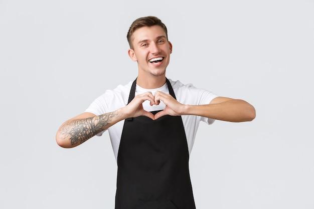 Koncepcja pracowników, sklepów spożywczych i kawiarni. przyjazny szczęśliwy kelner w czarnym fartuchu kochający gości, zapraszający do odwiedzenia kawiarni i delektowania się napojami, pokazujący znak miłości serca, białe tło