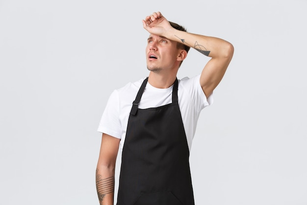 Koncepcja pracowników, sklepów spożywczych i kawiarni. zmęczony kelner patrzący w górę i wydychający ze zmęczenia, barista ociera pot z czoła, potrzebuje przerwy, czuje się wyczerpany stoły do serwowania, białe tło