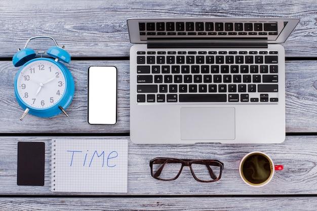 Koncepcja pracy czasu i biura. laptop z budzikiem i filiżanką kawy na białym drewnianym stole.