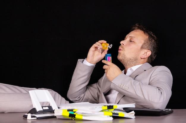 Koncepcja pracy niezależnej lub zdalnej. biznesmen w biurze uruchamia kulki mydlane.