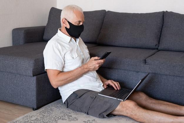 Koncepcja pracy online. poważny starszy mężczyzna w masce medycznej pracuje lub studiuje w domu na swoim komputerze przenośnym