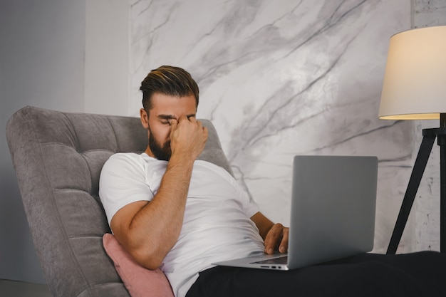 Koncepcja pracy, przepracowania i zmęczenia ludzi. zdjęcie stylowego zmęczonego freelancera siedzącego na kanapie z laptopem, wyczerpanego podczas pracy nad pilnym projektem późno w nocy, masującego grzbiet nosa