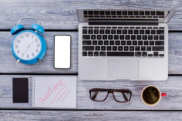 Koncepcja pracy w godzinach nadliczbowych. laptop z budzikiem i filiżanką kawy na drewnianym stole.
