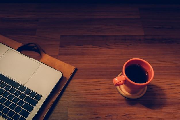 Koncepcja pracy w godzinach nadliczbowych w nocy. filiżanka kawy i laptop w świetle lampy.