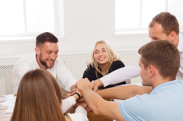 Koncepcja pracy zespołowej i teambuilding w biurze, ludzie łączą rękę