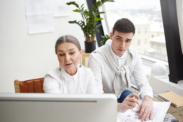 Koncepcja pracy zespołowej, współpracy i współpracy. zespół dwóch kreatywnych, wykwalifikowanych architektów, starsza kobieta i młody mężczyzna siedzący przed komputerem, prowadzący burzę mózgów i wspólnie omawiający rysunki