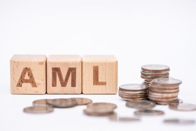 """Koncepcja prania pieniędzy, drewniany blok słów """"aml"""" na kawałku monet."""