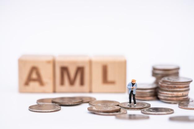 """Koncepcja prania pieniędzy. miniaturowi ludzie, przestępca finansowy na stosie monet i drewniany blok słów """"aml"""""""