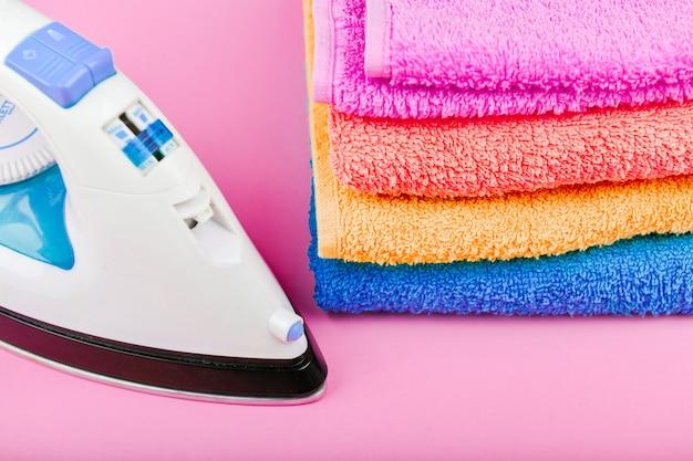 Koncepcja prasowania odzieży. zamówienie domu. żelazo i prasowana tkanina. żelazko elektryczne na różowej przestrzeni z ręcznikami. ręczniki w wielu kolorach.