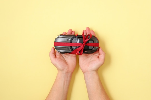 Koncepcja prezent na samochód. ludzki mienie w rękach na palmie bawi się samochód z czerwonym faborkiem na żółtym tle. widok z góry, płaska kompozycja. najlepsza oferta samochodów na sprzedaż, wynajem, szablon. prezentacja, pojazd pokazowy.