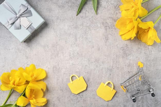 Koncepcja prezentów świątecznych na dzień matki zakupy pozdrowienie projekt z bukietem kwiatów żółtego tulipana na szarym tle
