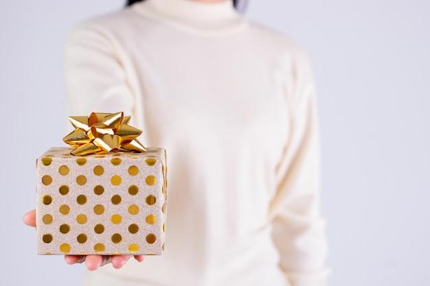 Koncepcja prezenty czasowe - pudełko ze złotą kokardką w ręku dziewcząt. koncepcja bożego narodzenia lub drugiego dnia świąt bożego narodzenia. koncepcja urodzinowa.