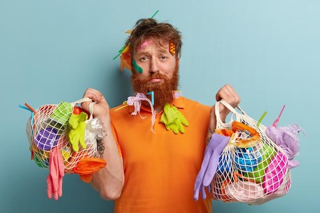 Koncepcja problemu recyklingu i zanieczyszczenia tworzywami sztucznymi. niezadowolony rudy mężczyzna z grubym włosiem, ma śmieci tkwiące we włosach i brodzie, nosi dwie torby pełne śmieci, odizolowane na niebieskiej ścianie