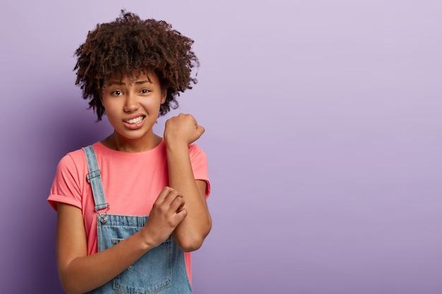 Koncepcja problemu skóry. niezadowolona samica afro drapie swędzące ramię