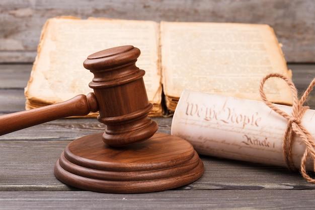 Koncepcja procesu retro sądowego. drewniany młotek z książką i zwojem.