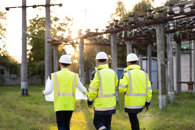 Koncepcja produkcji energii elektrycznej w przemyśle elektrycznym widok z tyłu grupa różnorodnych specjalistów