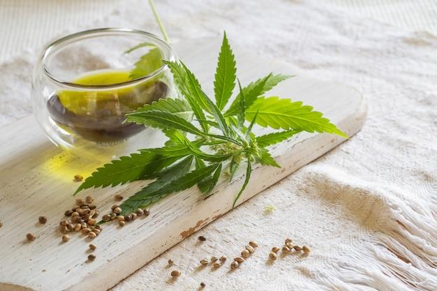 Koncepcja produktów konopnych. nasiona, olej konopny i zielona roślina na białym samodziałowym materiale