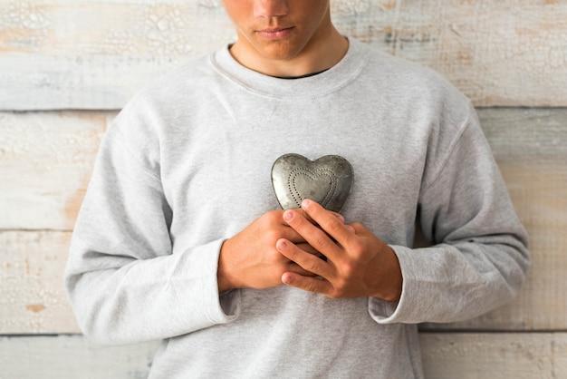 Koncepcja profilaktyki i zdrowego stylu życia - mężczyzna trzymający metalowe serce z drewnianą szarą ścianą w tle