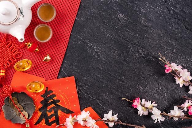 """Koncepcja projektowa chińskiego księżycowego stycznia nowego roku - świąteczne akcesoria, czerwone koperty (ang pow, hong bao), widok z góry, płaska konstrukcja, nad głową powyżej. słowo """"chun"""" oznacza nadchodzącą wiosnę."""