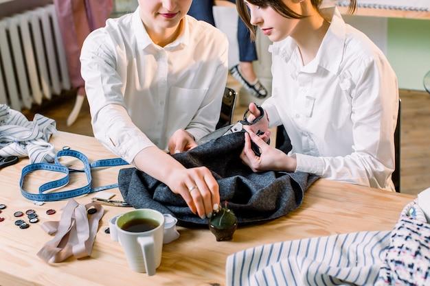 Koncepcja projektowania mody. zdjęcie z boku dwóch pięknych dziewczyn krawcowych w trakcie pracy. szwalnia robótki.