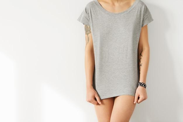 Koncepcja projektu koszulki. przycięte zdjęcie młodej europejskiej modelki ubranej w szarą, długą casualową koszulkę