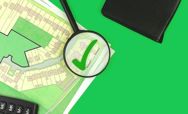Koncepcja projektu nieruchomości, szkło powiększające wyszukuje działkę na sprzedaż, zdjęcie backgorund budowy domu, zielone biurko, widok z góry i przestrzeń do kopiowania