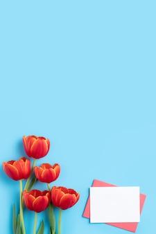 Koncepcja projektu prezentu z pozdrowieniami świątecznymi na dzień matki z bukietem czerwonych tulipanów i karty na jasnym niebieskim tle stołu