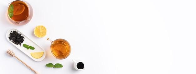 Koncepcja projektu widok z góry miodowej czarnej herbaty z żółtą cytryną i liściem mięty na białym tle stołu.