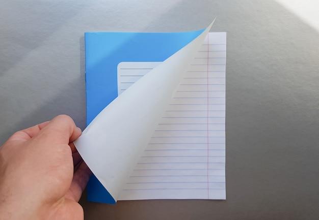 Koncepcja projektu - widok z góry wysokiej jakości męskiej ręki przeglądając arkusz niebieskiego notatnika w paski. widok z góry, kopia przestrzeń, układ płaski.