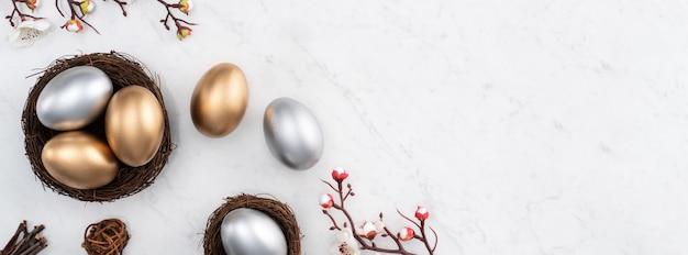 Koncepcja projektu złote i srebrne pisanki w gnieździe z białym kwiatem śliwki na jasnym marmurowym białym tle stołu.