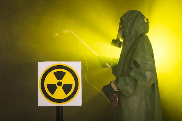 Koncepcja promieniowania, zanieczyszczenia i niebezpieczeństwa - mężczyzna w odzieży ochronnej i masce gazowej na ciemnym tle