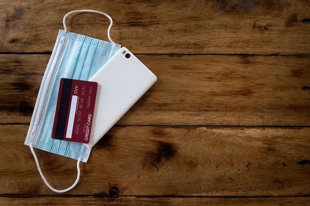 Koncepcja przebywania poza domem podczas epidemii, covid-19, maska na twarz, smartfon i karta kredytowa. ułożone jeden na drugim na drewnianej podłodze