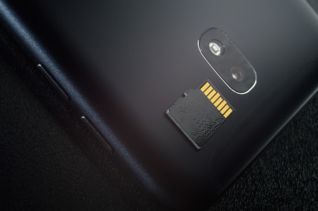 Koncepcja przechowywania pamięci flash: karta micro sd na tle smartfona. karta pamięci służy do przechowywania informacji cyfrowych w przenośnych urządzeniach elektronicznych, takich jak telefony komórkowe, tablety itp.
