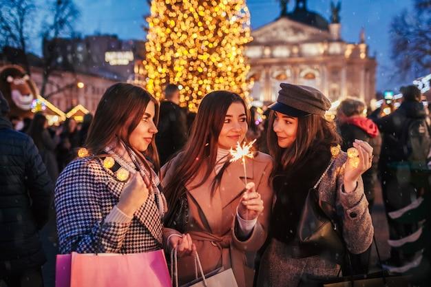 Koncepcja przeddzień nowego roku. przyjaciółki palą zimne ognie we lwowie przy choince na jarmarku ulicznym z okazji świąt. szczęśliwe dziewczyny trzymając torby na zakupy pod śniegiem. przyjęcie